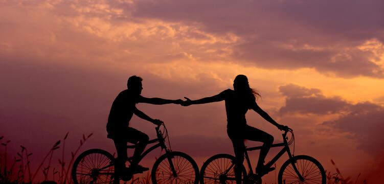 couple holding hands while bike riding