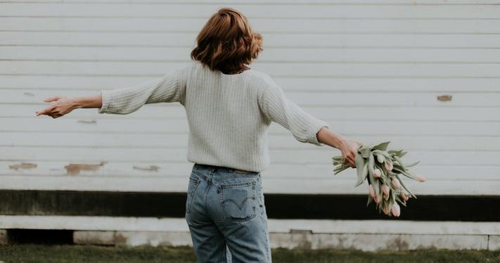 woman spinning around, holding flowers